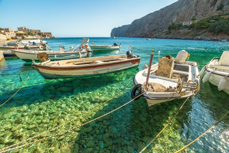 mani: Fishing boats in the clear tropical waters of Gerolimenas, Mani Peninsula, Lakonia, Peloponnese, Greece.