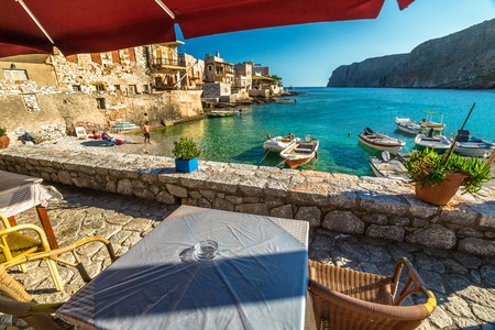 mania: Gerolimenas village, Mania Peninsula, Lakonia, Peloponnese, Greece - August 23, 2015: Typical tavern greek on waterfront between mountains and bay with tropical waters, stone beach and fishing boats.