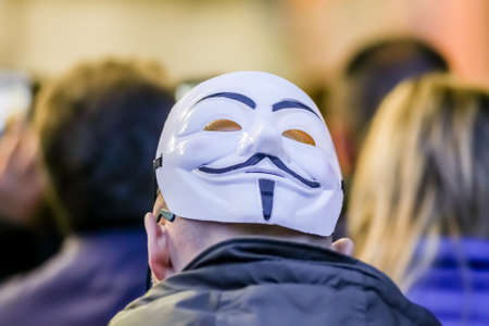 guy fawkes mask: Anonimous rear man wearing Guy Fawkes mask during a street protests