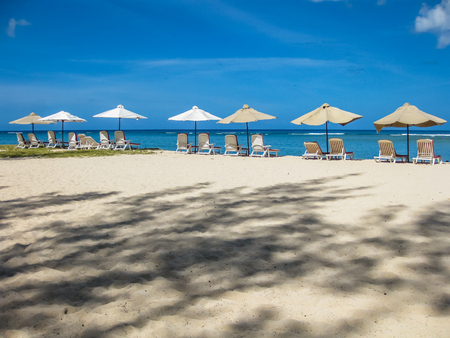 sun umbrellas: Sun umbrellas and chaise longues in the famous tropical Central Beach with white sand, Flic en Flac in the west part of Mauritius, Indian Ocean, Africa.
