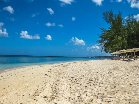 sun umbrellas: The famous tropical Central Beach with white sand, Flic en Flac in the west part of Mauritius, Indian Ocean, Africa. Sun umbrellas and chaise longues. Stock Photo