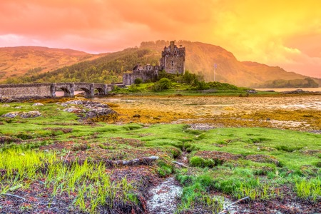 confluence: Dornie, Kyle of Lochalsh, Scotland, United Kingdom - May 31, 2015:Eilean Donan Castle at sunset, Dornie, Kyle of Lochalsh in Scotland, United Kingdom. It is the most visited castle, situated on an island at the confluence of three sea lochs.