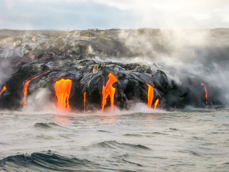 kilauea: Sea view of Kilauea Volcano in Big Island, Hawaii, United States. A restless volcano that has been in business since 1983. Shot taken at sunset when the lava glows in the dark as jumps into the sea.