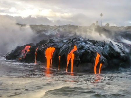 restless: Sea view of Kilauea Volcano in Big Island, Hawaii, United States. A restless volcano that has been in business since 1983. Shot taken at sunset when the lava glows in the dark as jumps into the sea.