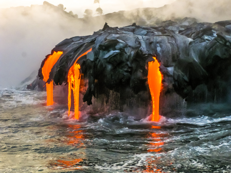 huge: Sea view of Kilauea Volcano in Big Island, Hawaii, United States. A restless volcano that has been in business since 1983. Shot taken at sunset when the lava glows in the dark as jumps into the sea.