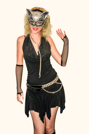 skimpy: Attractive woman in skimpy black dress, fishnet, stockings, platform boots and silver cat mask kneeling on polished wooden floor at Halloween party. .