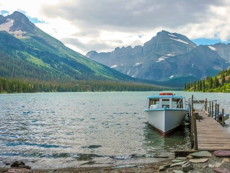 Glacier National Park: Fishing boat docked at the wooden jetty at Lake McDonald, Glacier National Park, Montana, United States. Stock Photo