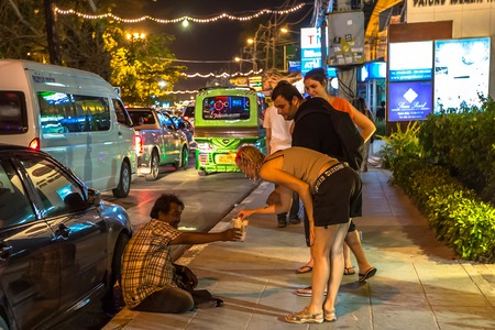 hombre pobre: Patong Beach, Phuket, Thailand - January 1, 2016: kind tourists  giving charity to a   local poor man on the street at night.
