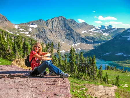 alpine tundra: Young and smiling tourist resting in the Hidden Lake Overlook after a hiking. Glacier National Park, Montana, United States.