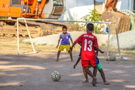 playing the market: Fish market, Rawai, Phuket, Thailand - January 7, 2016: Happy children playing soccer in a sand field behind the famous fish market.