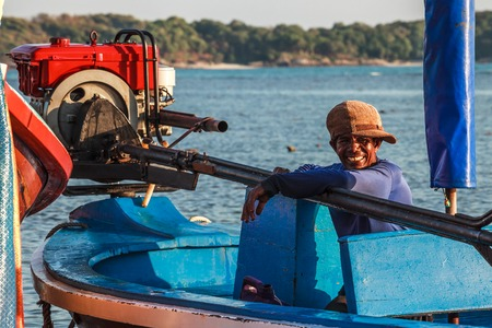 Rawai Beach, Phuket, Thailand - January 9, 2016: local fisherman with his typical long-tail boat with diesel engine, resting after an hard day of work in Rawai beach in the late afternoon, comtempling the warm setting sun Editorial