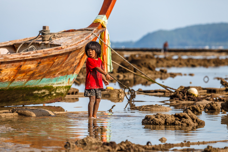 Sea Gypsy Village, Rawai, Phuket, Thailand - January 10, 2016: amazed young child pointing finger at the low tide in Rawai Beach in the late afternoon. Typical long-tail boat on the background.