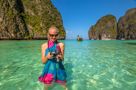 Smiling professional photographer with colorful blue and pink sarong, checks his camera. Maya Bay, famous lagoon of The Beach movie with Leonardo DiCaprio, Phi Phi Leh, Andaman Sea in Thailand. Stock Photo