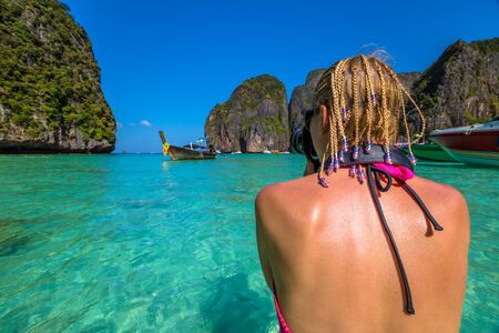 andaman sea: Back of professional travel photographer with camera while shooting a typical Long Tail Boat at Maya Bay, famous lagoon of The Beach movie with Leonardo DiCaprio, Phi Phi Leh, Andaman Sea in Thailand.