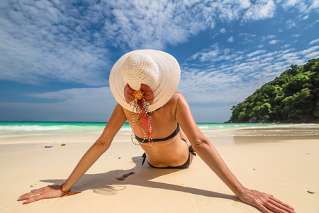 similan islands: Beautiful woman with swimsuit and wide-brimmed hat relaxing on white sand tropical beach. Similan Islands National Park, Phang Nga, Thailand, one of the tourist attraction of the Andaman Sea. Stock Photo