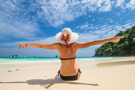 similan islands: Beautiful and happy woman with swimsuit and wide-brimmed hat on white sand tropical beach. Similan Islands National Park, Phang Nga, Thailand, one of the tourist attraction of Andaman Sea.