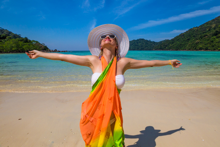 Happy and attractive woman with yellow sarong and white wide-brimmed hat on tropical beach of Koh Surin Nuea, North Surin Island National Park, Phang Nga, Andaman Sea, Thailand