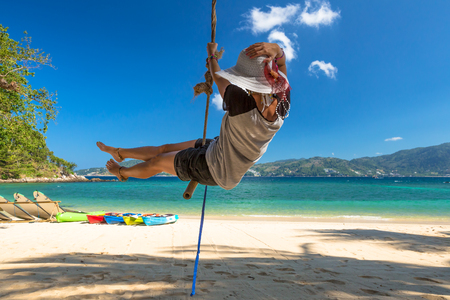 Happy woman with shorts, shirt and wide-brimmed hat swinging in Paradise Beach, the most famous beach in Patong, Phuket, Thailand. On background blue tropical sea, kayaking and white sand.