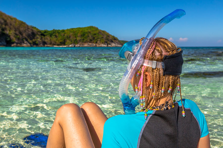 Closeup of snorkeler with braids, wetsuit snorkel, mask and fins, seen from behind, sitting on the shore in blue tropical sea. Racha Noi island, Rawai provinces, Andaman Sea, Thailand. Stock Photo