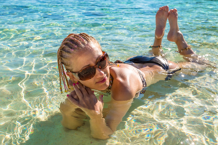 blue and white: Attractive sexy girl with braids, sunglasses and leopard print bikini enjoying sunny day on tropical crystal beach. Beautiful girl sunbathing under summer sun lying in sand on beach with blue water. Stock Photo