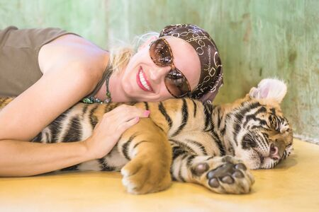 dangerous love: Smiling beautiful woman with sunglasses, embraces a little tiger, Panthera Tigris, lying in Thailand. Concepts of courage, fun and dangerous.