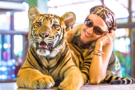 donna innamorata: Sorridente bella donna con occhiali da sole, abbraccia una piccola tigre, Panthera Tigris, seduto in Thailandia. Concetti di coraggio, divertimento e pericoloso.