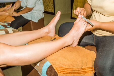 beauty center: Close up of manicurist doing pedicure in a Thai beauty center. Stock Photo