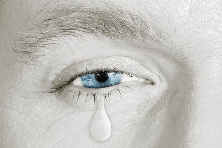 Crying blue eye on black and white face. concept of sadness, fear,love pains, mental depression disease,  eyewash and eye health