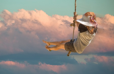 Young woman with shorts, shirt and wide-brimmed hat swinging with sunset sky and cloud background. Freedom concept.