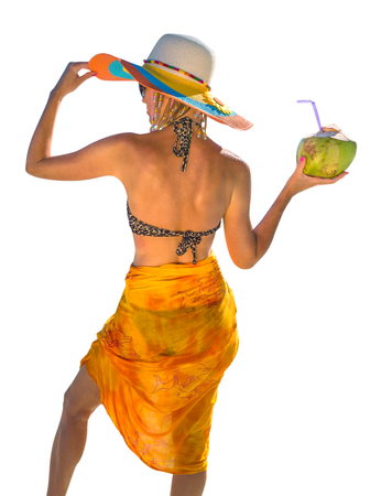 Rear view of attractive and tanned woman with yellow sarong and wide-brimmed hat while holding a coconut fresh cocktail.  Isolated on white background. Stock Photo