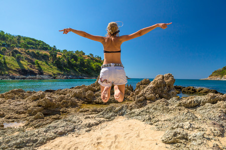 nui: Happy woman with bikini and shorts, jumping in the air on Ya Nui Beach, a little cove divided by a rocky cape, Phuket, Thailand, Asia.