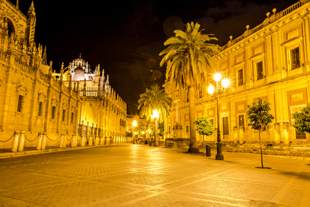 historic buildings: The Cathedral of Seville illuminated by night, with street and historic buildings around, the worlds largest Gothic Cathedral and the third religious building to size, Andalucia, Spain.