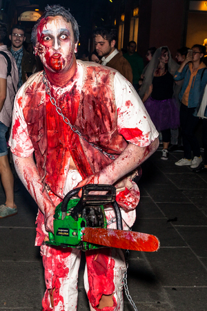 maniac: Bologna, Italy - May 21, 2016: Bologna zombie apocalypse walk. Halloween costume maniac with bloody clothes and chainsaw and scares people.