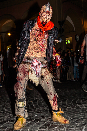 terrifying: Bologna, Italy - May 21, 2016: Bologna zombie apocalypse walk. A frightening and terrifying zombies walking down the street at night.