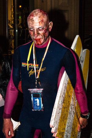 siervo: Bolonia, Italia - 21 de mayo, 2016: zombis que practica surf con tabla de servidumbre con la mordedura de tiburón durante el desfile de la noche: Bolonia apocalipsis zombie paseo. Editorial