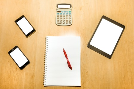 paper screens: Flat lay of an office desktop wooden table with mobile phones, tablet pad, calculator and a notepad with red pen. Blank screens and paper for copy space