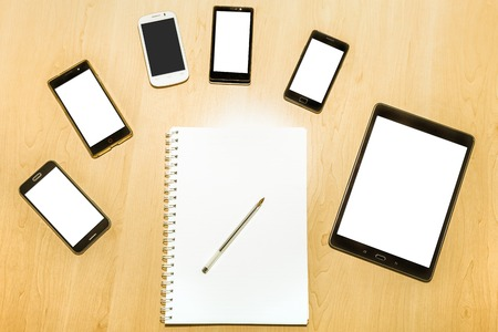 paper screens: Flat lay of a business desk with mobile phones, tablet pad, and notepad with pen and paper. Blank screens and paper for copy space