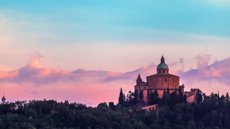 San Luca basilica church on Bologna hill, in a colorful twilight. pink and blue. in Italy