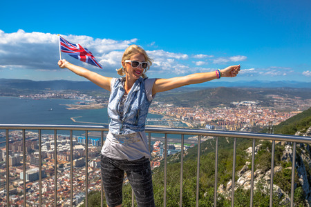 Woman enjoy with the British flag in hand on top of Gibraltar Rock. Gibraltar is a territory of South West Europe Which is part of the United Kingdom.
