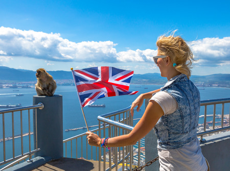 observes: Tourist woman holding an English flag observes one of the famous monkeys of Gibraltar from the top of Gibraltar Rock, in the Upper Rock Natural Reserve.