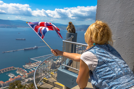 bandera inglesa: Tourist woman holding an English flag observes one of the famous monkeys of Gibraltar from the top of Gibraltar Rock, in the Upper Rock Natural Reserve.