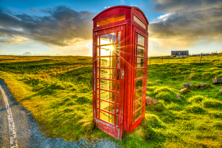 Urban red telephone box in the middle of a green countryside. Concept for synergy between modern and rural area. Red and green complementary colors join together in a scottish land, United Kingdom. Stock Photo
