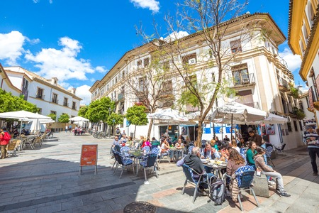 Cordoba, Andalusia, Spain - April 20, 2016: tourists while dining in restaurants of typical Barrio de la Juderia, famous for its narrow streets.