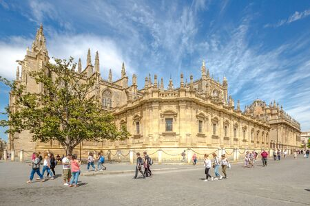 Seville, Andalusia, Spain - April 18, 2016: people walk next to the Cathedral of Seville and Giralda, the world's largest Gothic Cathedral and the third religious building to size.