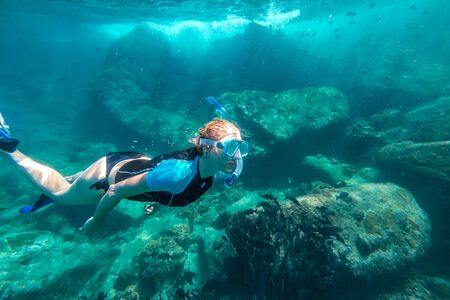 similan islands: Young lady snorkeling over coral reefs in a tropical sea. Similan Islands in Thailand, one of the tourist attraction of the Andaman Sea. Stock Photo