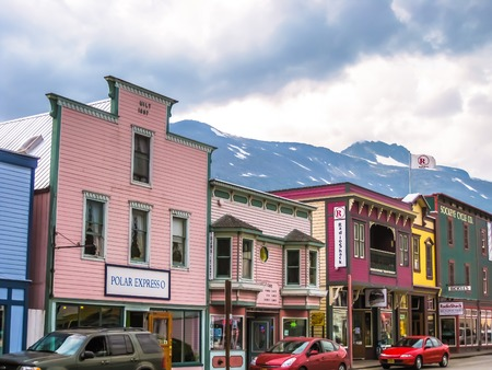 come in: Skagway, Alaska, United States - August 7, 2009: Klondike Gold Rush National Historic Park. Historic buildings are interspersed with new modern buildings. Its streets seem to come from in another age.