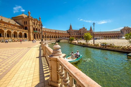 Seville, Andalusia, Spain - April 18, 2016: panoramic view of boats with tourists on canal surrounding the Plaza de Espana on a sunny day. Editorial