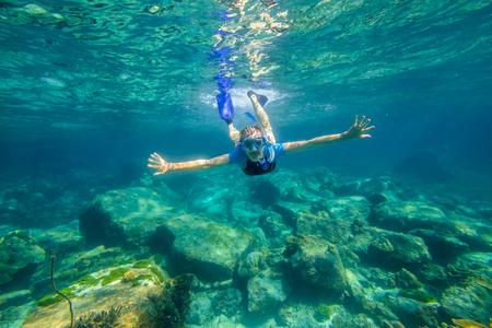 apnea: Young female snorkeling in tropical sea. Woman apnea swims in coral reef. Stock Photo