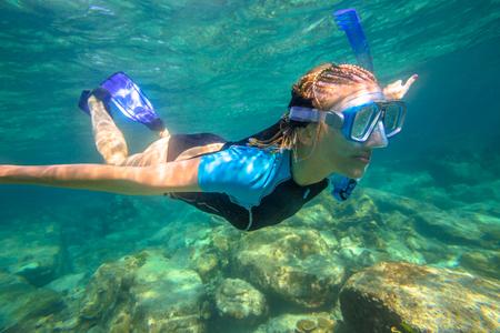 Close up of female apnea swims in tropical turquoise sea of Racha Noi, Phuket in Thailand. Stock Photo