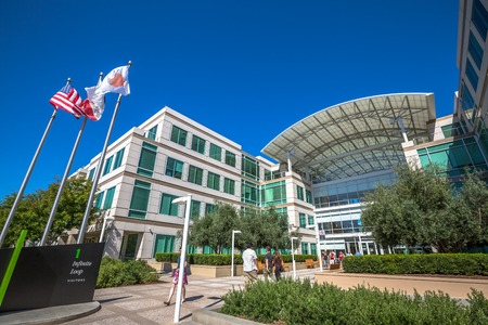 Cupertino, CA, USA - August 15, 2016: people walk in front of the Apple world headquarters at One Infinite Loop. Apple is a multinational corporation that produces technology devise.